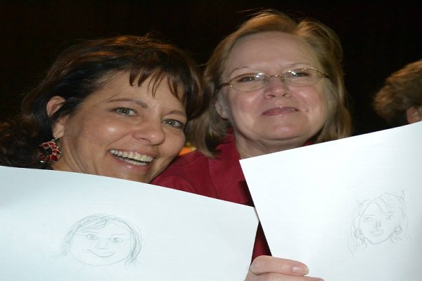 Two Women Holding Drawings